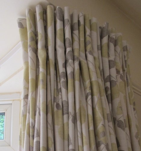 Handmade pinch pleated curtains inVilla Nova fabric fitted on a metal track which has been reverse bent around a bay window in Goring By Sea in Goring